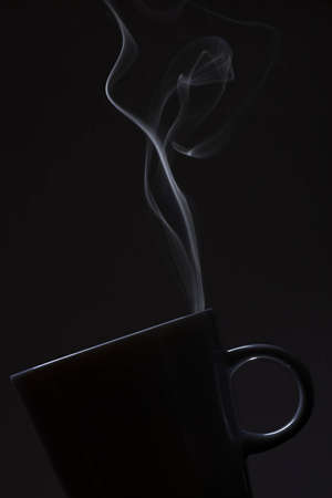 Steaming cup of coffee or tea on dark background photo