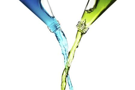 liquids: Mixing blue and green liquids from bottles Stock Photo