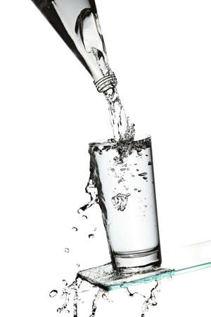 overflow: Overflowing fresh water into a glass on a glass surface Stock Photo
