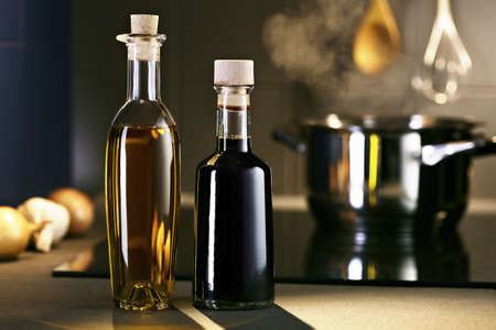 ceramic bottle: Oil and vinegar in front of hob with steaming pot