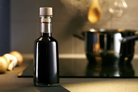 ceramic bottle: Vinegar in front of hob with steaming pot