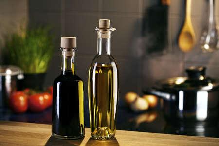 aceite de cocina: Aceite y vinagre en la frente de cocina con una olla humeante Foto de archivo