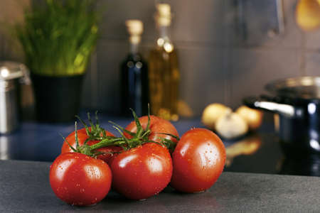 Some tomatoes in front of hob with steaming pot photo