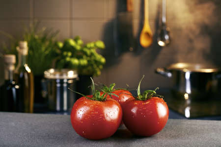Tomatoes in front of hob with steaming pot photo