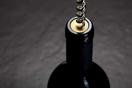 cork screw: Opening a bottle of red wine with a cork screw Stock Photo