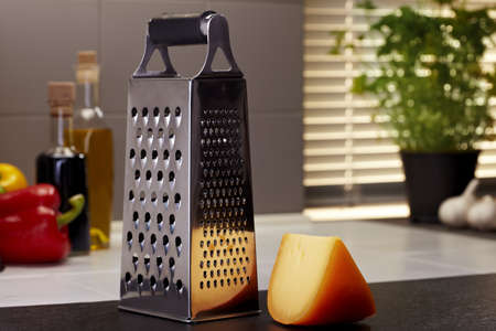 Gouda cheese with a grater in a kitchen photo