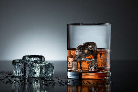 bourbon: Whiskey glass with wet ice cubes on black surface