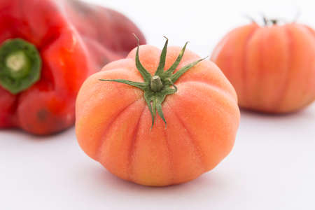 Two raf tomatoes with red pepper on white background
