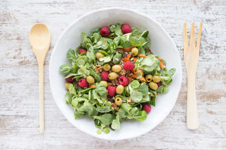 Salad of canons, raspberries, raisins, olives, nuts, carrots and pips on white wooden background. Wooden spoon and fork.