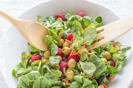 Salad of canons, raspberries, raisins, olives, nuts, carrots and pips. Wooden spoon and fork.