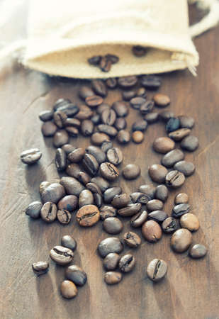 Coffee beans with cloth sack on wooden background