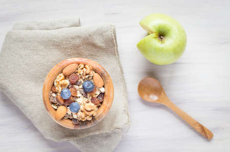 Healthy breakfast with muesli, almonds, blueberries, walnuts on white background. Top view. Wooden spoon.