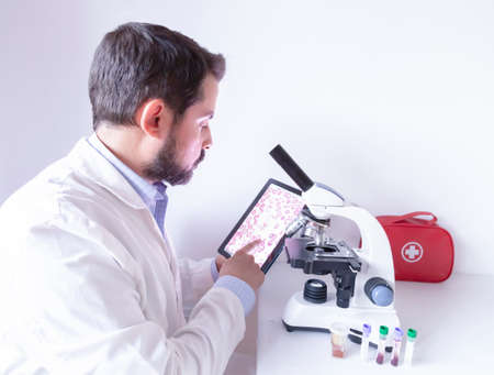 Doctor looking on digital tablet computer and working on microscope in hospital laboratory. Scientist testing blood sample in laboratory. Фото со стока - 131824087