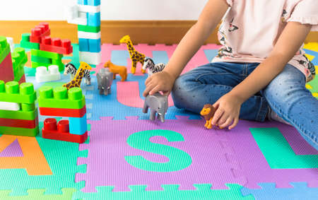 Little girl playing with animal toys at home or kindergarden. Playroom.