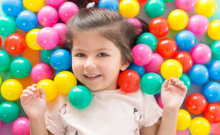 Little smiling girl playing lying in colorful balls park playground.