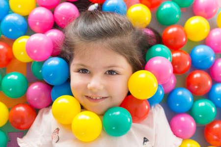 Mała uśmiechnięta dziewczyna gra leżąc w kolorowe kulki parku zabaw.