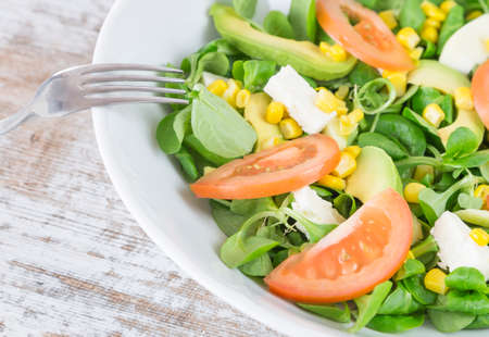 Organic salad leaves: arugula, watercress, lettuce, corn and tomato in a bowl. Close up. Fork supported. Healthy food concept. Banco de Imagens