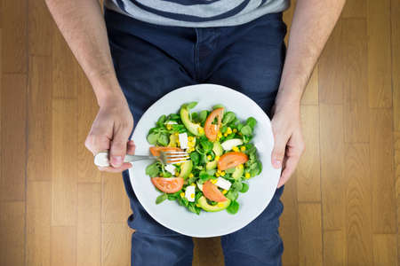 Young man in jeans eating tasty salad with vegetables while sitting on the floor. Healthy food concept.