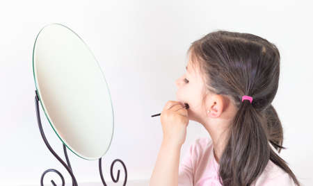 At home, in the bedroom, Little Girl Play to put on Makeup, combing hair together. Concept: beauty, family, fun at home.