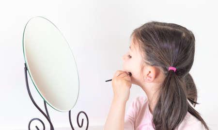 A la maison, dans la chambre, Little Girl Play se maquille en se coiffant. Concept : beauté, famille, plaisir à la maison.