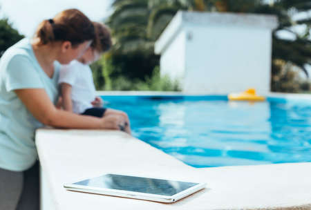 Digital Tablet photo in the foreground with mother and son playing in the pool in the background. Concept of the digital switch-off. Selective focus.