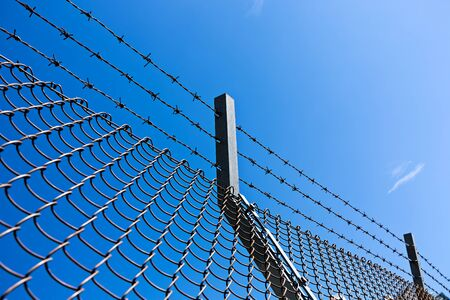 barbed wire frame: Razor Wire Above a Fence