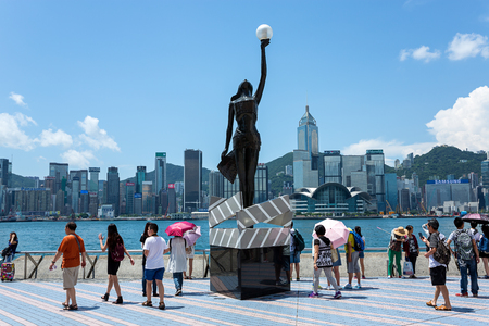 Tsim Sha Tsui, Hong Kong, China - July 28 2015: Bronze statue of Hong Kong Film Awards and skyline in Avenue of Stars in Tsim Sha Tsui East Promenade. The promenade honours celebrities of the Hong Kong film industry as the famous city attraction.
