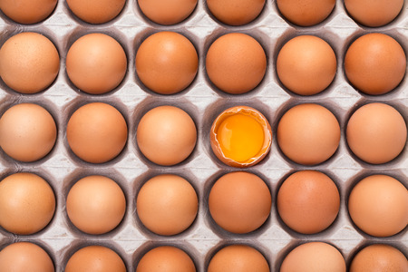 Cardboard tray filled with brown eggs, one egg is broken Stock Photo