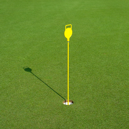 Golf hole in the green field Stock Photo