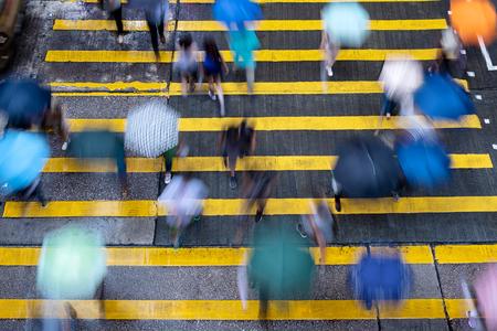 Motion blurred pedestrians crossing Hong Kong street in the rain