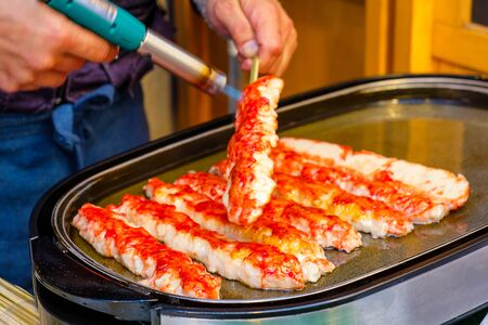 Fresh tender meat from the legs of a king crab blow torch in Tsukiji Market, Tokyo