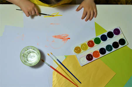 Children's hands when drawing. Desktop. Hobby. Table, colored, white and painted paper. Preschool classes. Child development, imagination