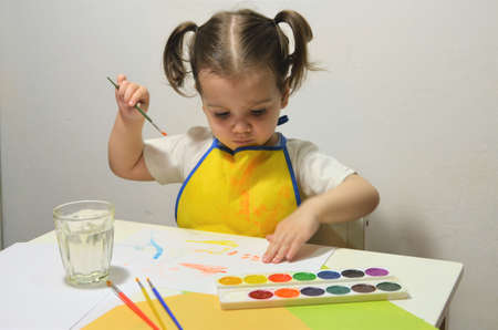 The girl draws watercolors with her fingers.
