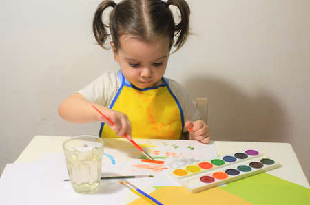 The little girl draws enthusiastically