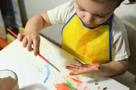 A girl at the table draws watercolors on paper