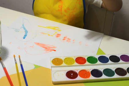 Childrens hands, yellow apron. Watercolors, brushes, multi-colored, white painted paper.