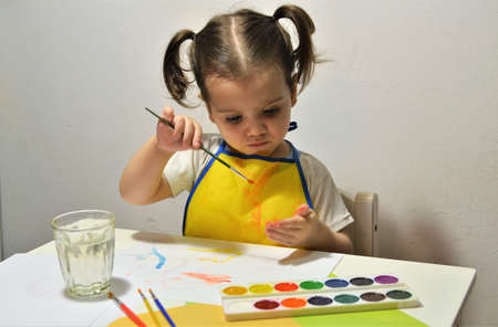 A little girl at the table draws on her fingers