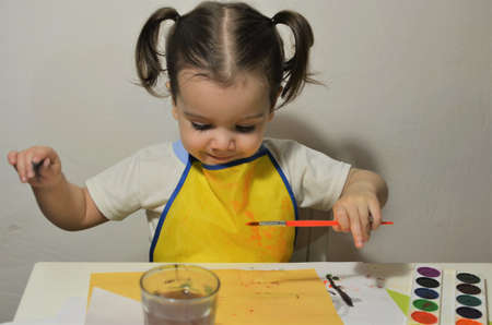 A little girl paints in watercolors Banco de Imagens