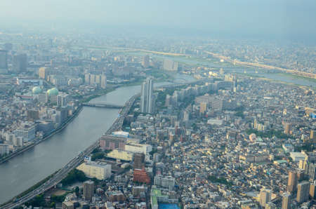 From a height of flight. River with bridges inside urban. 報道画像