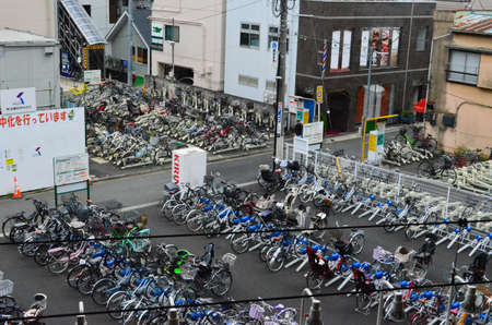 A row of bicycles parked on the side of a building 報道画像