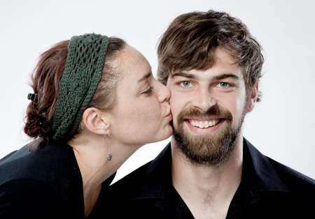 Young woman giving smiling kiss on his cheek