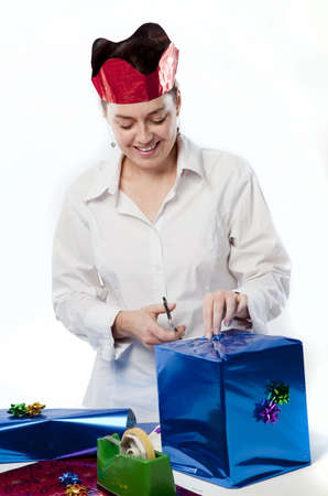 Pretty young woman preparing gifts and decorations for Christmas. Stock Photo - 5911562