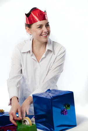 Pretty young woman preparing gifts and decorations for Christmas. Stock Photo - 5911551