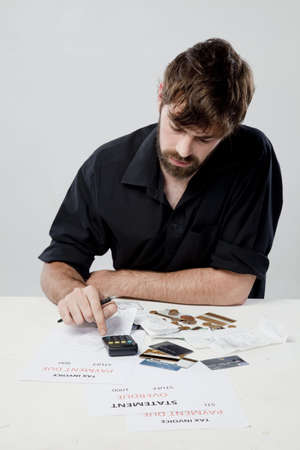Man budgeting using a calculator photo