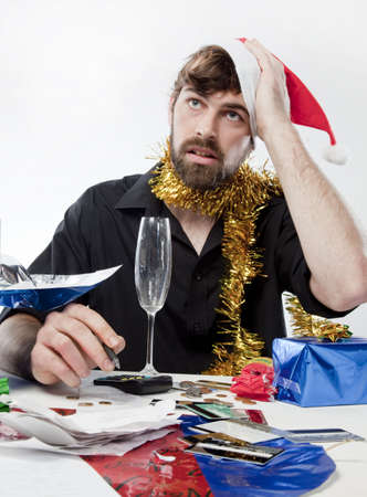 Man in Santa Claus hat loooking overwhelmed about his finances photo