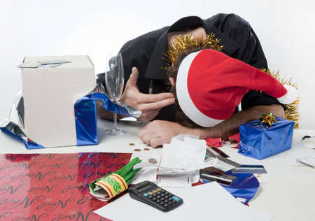 Man in Santa Claus hat loooking depressed about his finances photo