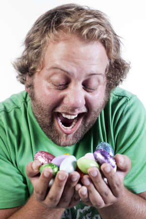 Caucasian young man holding handful of colourful easter egg candy. photo