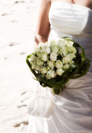 Close up on white roses bouquet and dress of bride
