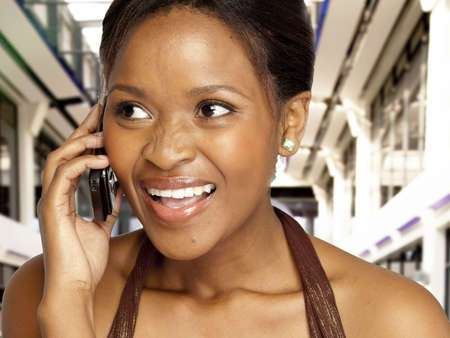 Beautiful South African woman speaking on cell phone with a smile. photo
