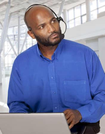 repondre au telephone: Entreprise entrepreneur africain qui cherche s�rieux tout en conversant sur son casque de voip et de travailler sur son ordinateur portable.  Banque d'images